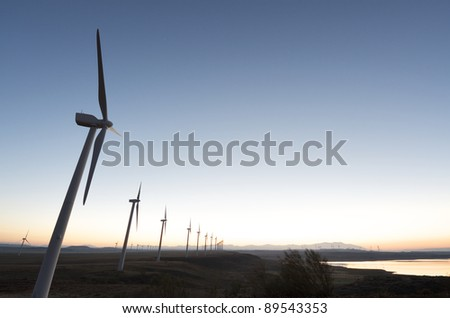 aligned windmills for renowable electric production at sunset