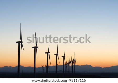 aligned windmills for renowable electric production at sunset - stock photo