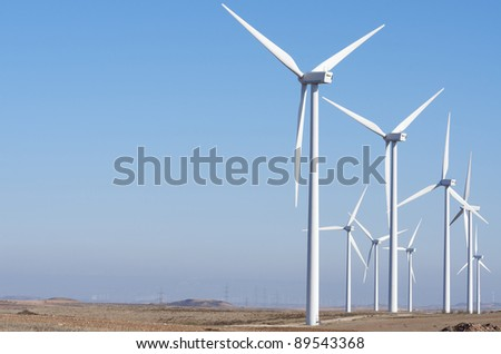 aligned windmills for renowable electric production with clear sky - stock photo