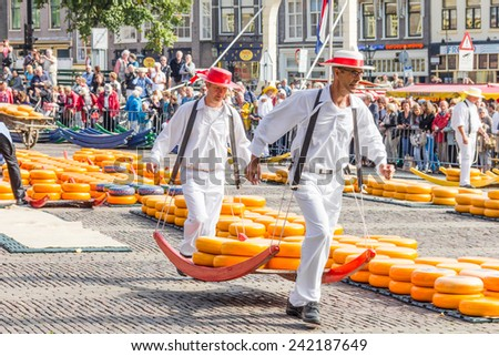 ALKMAAR, THE NETHERLANDS - SEPTEMBER 7: Carriers walking with many cheeses in the famous Dutch cheese market, September 7, 2012 in Alkmaar, The Netherlands. The event happens in the Waagplein square. - stock photo