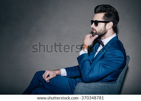 All about style. Side view of young handsome man in suit and bow tie holding hand on chin and looking away while sitting in grey chair against grey background - stock photo