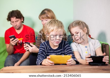 All family, kids and parents sitting with gadgets, playing the games in smartphones - stock photo