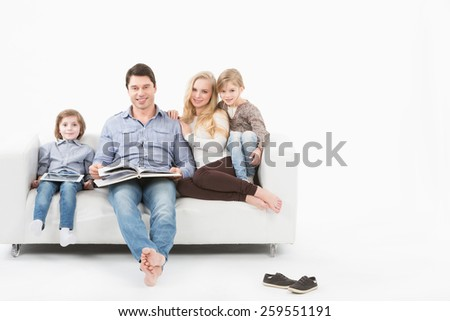 All family sitting on a white sofa on a white background and reading a book. - stock photo