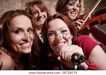 All-girl band performing in stylish clothing - stock photo