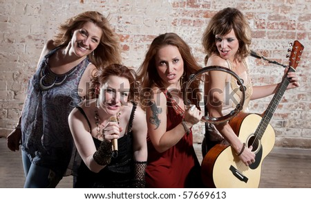 All-girl band performing in stylish clothing at a warehouse - stock photo