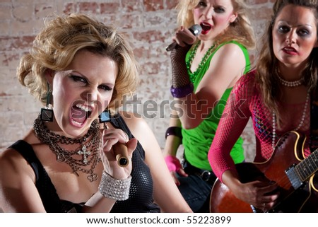 All-girl punk rock band performs in front of a brick background - stock photo