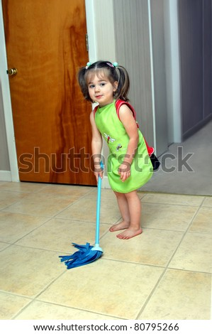 All hands on deck!  This little girl is ready and willing to help her mother with household chores.  She is wearing her apron, holding her dusting rag and wielding her mop. - stock photo