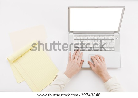 All hands on desk - overhead shot of hands typing on laptop with notepad - stock photo