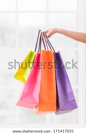 All I got on sale. Close-up of female hand holding multi colored shopping bags  - stock photo