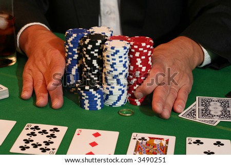 All in! Man pushes in all his chips and his gold wedding ring. - stock photo
