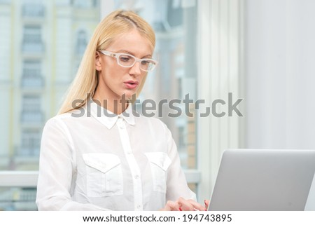 All in the mind.Businesswoman in glasses holding a pen near the head and thinking about work and looking up at the ceiling. Beautiful blonde woman.