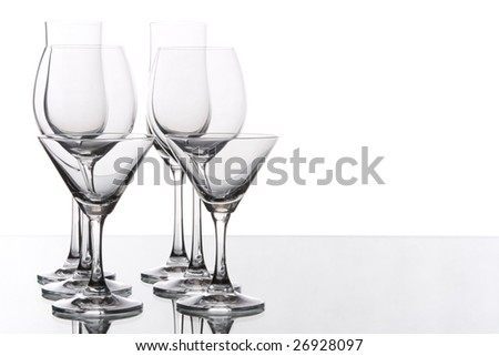 All kind of glasses are arranged in line against white background on the glass table.
