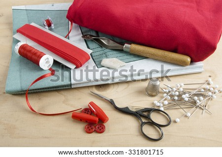 All kinds of sewing things like fabric, pattern paper, ribbon, sewing yarn, tailors chalk, buttons, thread spools, yarn puddles, tracing wheel, thimble, pins and a pair of scissors on a wooden table - stock photo