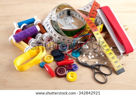 All kinds of tools and materials for sewing, like yarn, tape measure, buttons, ribbon, chalk, thread spools, yarn puddles, and pins, on a wooden underground - stock photo