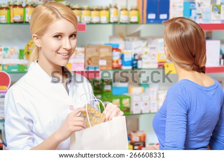 All medicines in the prescription. Portrait of a young smiling pharmacist holding a paper bag and a blister of pills with a female customer on the background