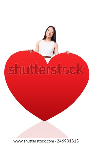 All my love is for you. Beautiful young Asian woman in pretty dress leaning at the huge red heart shaped valentine and smiling while standing against white background   - stock photo
