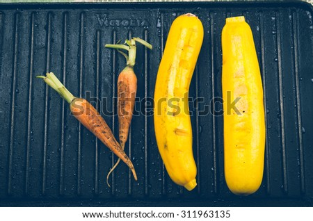all-natural Carrot and zucchini on black metal grill. - stock photo