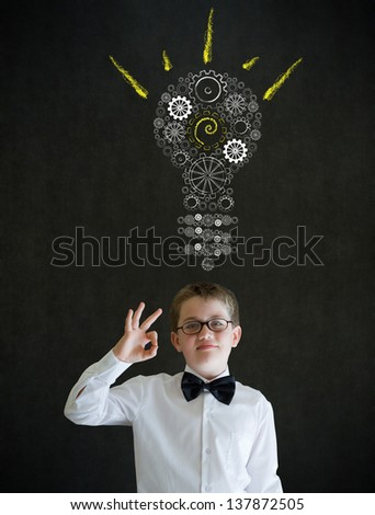 All ok or okay sign boy dressed up as business man with bright idea gear cog lightbulb on blackboard background - stock photo