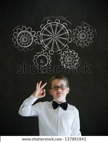 All ok or okay sign boy dressed up as business man with chalk turning gear cogs or gears on blackboard background - stock photo
