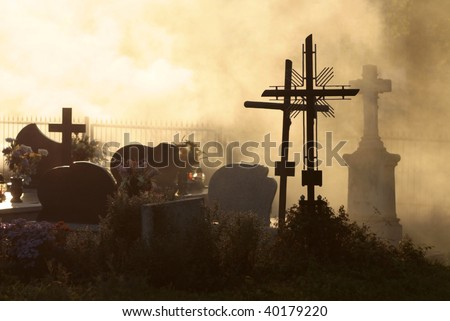 All Saints, cemetery at sunset with cross and silhouetted against sky,