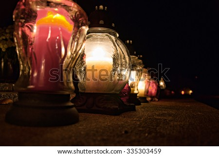 All Saints Day. Candles burning on graves at cemetery at night. All Hallows Eve / Day of All the Saints / Solemnity of All Saints / Feast of All Saints / 1st November / Happy Halloween / 31st October - stock photo
