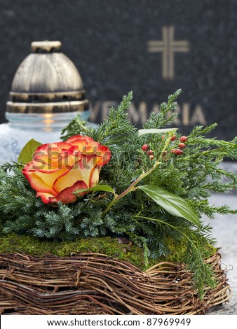 All Saints' Day in Poland. Floral decoration and a cemetery candle on a Christian grave. - stock photo