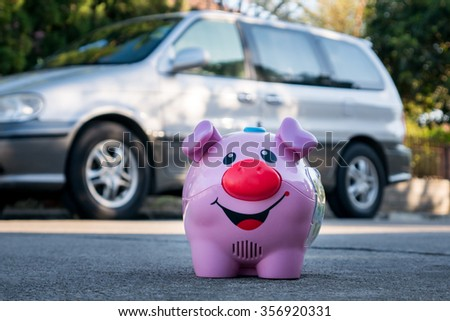 All savings money from pink ceramic piggy bank to pay for the dream car on blurred background - stock photo