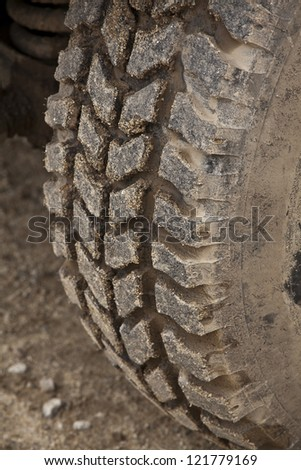 All terrain tire coated in mud. Detail of an off-road vehicle. - stock photo