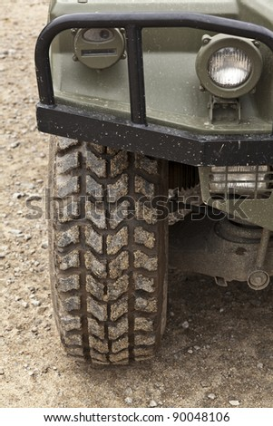 All terrain tire coated in mud. Detail of an off-road vehicle - stock photo