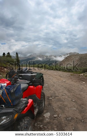 All-terrain-vehicle parked beside mountain trail with packs and helmets on cloudy day - stock photo