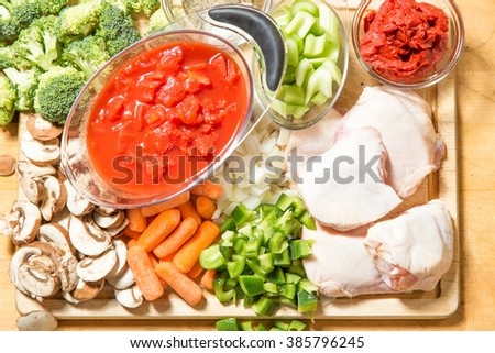 All the fresh raw ingredients for chicken cacciatore on chopping block ready to be assembled into a delicious dinner - stock photo