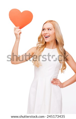 All thoughts about love. Beautiful young blond hair woman holding heart shaped valentine card and looking at it with smile while standing isolated on white - stock photo
