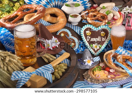 All typical German Bavarian symbols in one picture. Gingerbread heart with â??The beer is tappedâ?? text, soft pretzels, Bavarian veal sausage and beer.