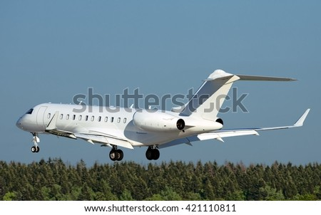 All white business jet gliding over the trees in great evening light - stock photo