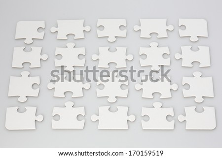 All white jigsaw puzzle with pieces symmetrically placed with space in between. - stock photo