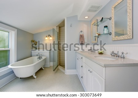 All white luxury master bathroom with vintage bathtub and tile floor. - stock photo