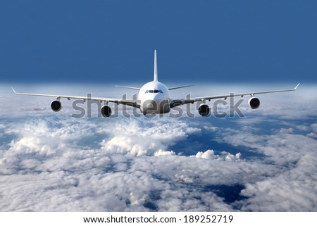 All white plane in the air in the clouds - stock photo