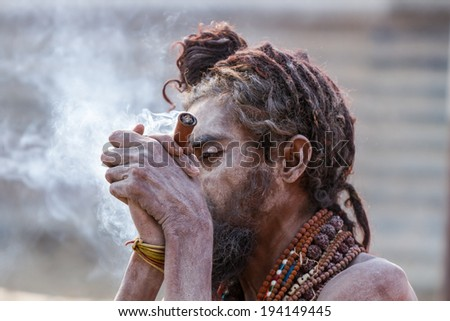 ALLAHABAD, INDIA - FEB 13 - A Hindu sadhu smokes a hash pipe during the festival of Kumbha Mela on February 13th 2013 at Allahabad, India. - stock photo