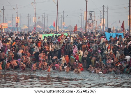 ALLAHABAD, INDIA - FEBRUARY 10, 2013: Thousands of Hindu devotees come to confluence of the Ganges and Yamuna River for holy dip during the festival Kumbh Mela. The world's largest religious gathering - stock photo