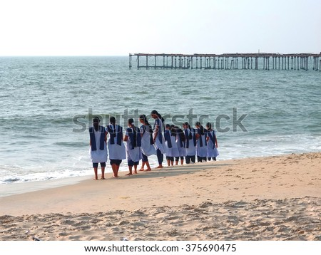 ALLEPPEY, INDIA - DECEMBER 30, 2013: Unknown high school girls on Alleppey beach in front of a pier which is 137 years old in Alleppey (also known as Alappuzha), Kerala, India.