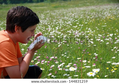 allergic child to pollen and flowers with a handkerchief while sneeze in the middle of meadow - stock photo