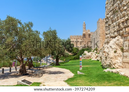 Alley along ancient walls as Tower of David on background in Old City of Jerusalem, Israel. - stock photo
