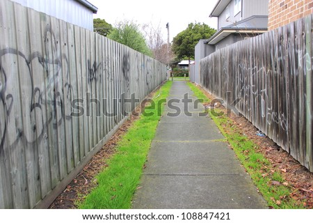 Alley way between homes with wooden fencing painted with graffiti and footpath with grey winters sky - stock photo