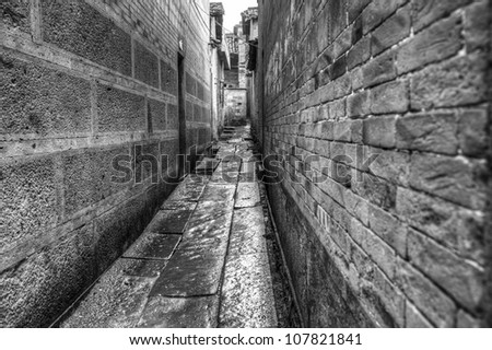 Alley way in an old town with ancient buildings under raining - stock photo