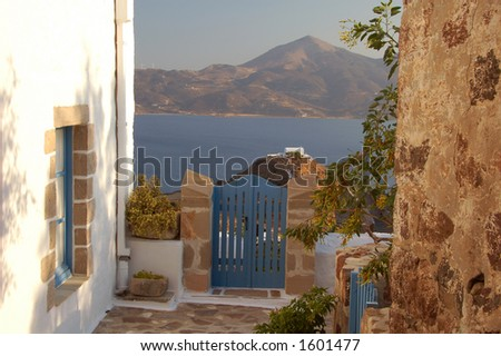alley with a view to a chapel in the distance at an island in Greece - stock photo