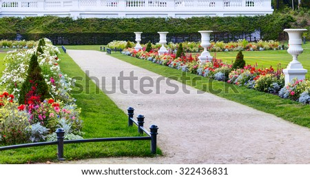 Alley with white flowerpots in the beautiful flowerbed. Lithuania. - stock photo