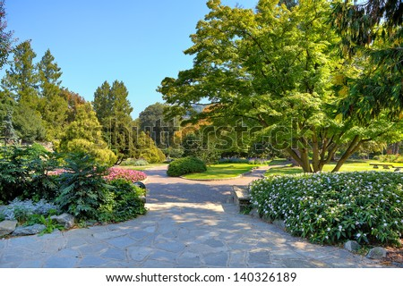 Alleys and walkways among green lawns and colorful trees at botanic garden named as Valentino Park in Turin, Italy. - stock photo