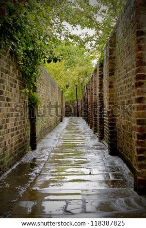 Alleyway with rain soaked pavement - stock photo