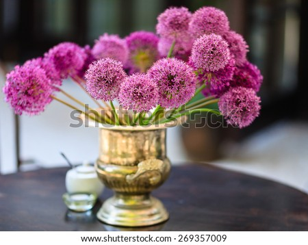 Allium flowers bouquet in a stylish metal decorative vase. Shallow depth of field - stock photo