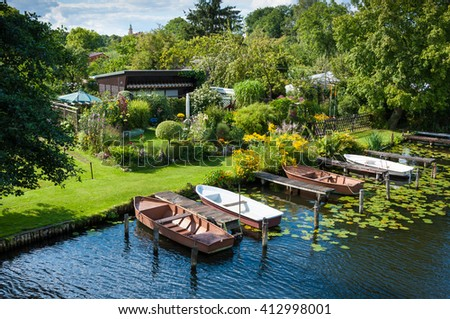 Allotment garden on the banks of a canal, very idyllic, green, flowers, boats. Sunshine. - stock photo
